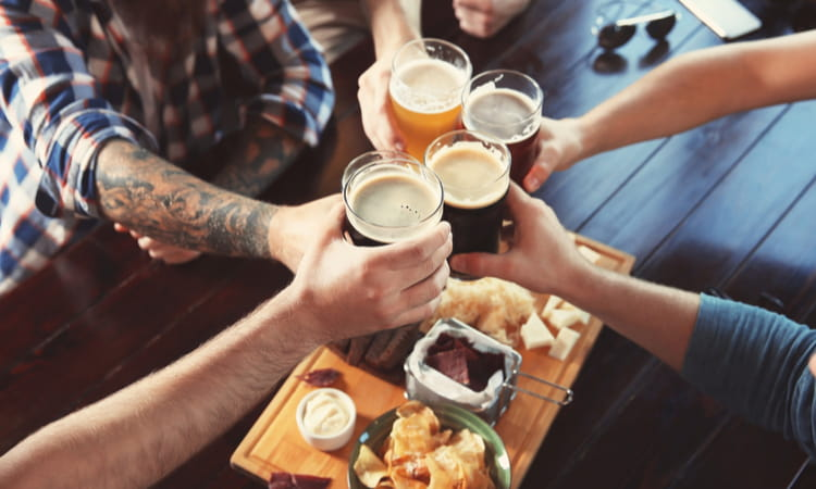 group toasting beer with bar food