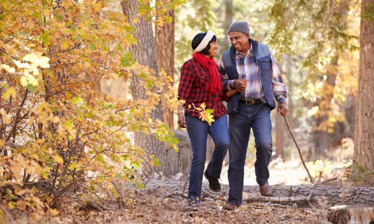 happy senior couple walks through fall foliage in Denver